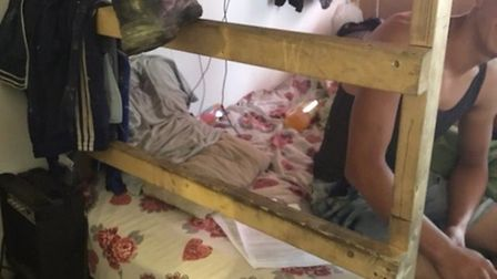 A man sits on a makeshift bunk at the converted one-room flat