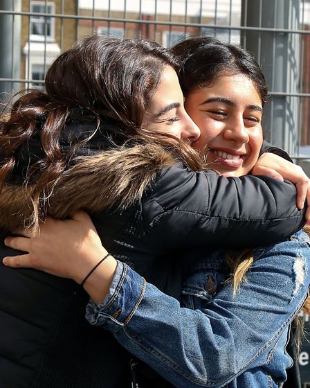 Selin Hasgul, left, hugs her friend Rukem Guvenc, after they both received an A* each in their GCSE