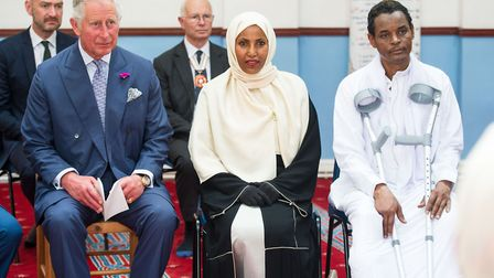 Prince Charles sits with Cllr Rakia Ismail and her husband Yassin Hersi on a visit to Muslim Welfare
