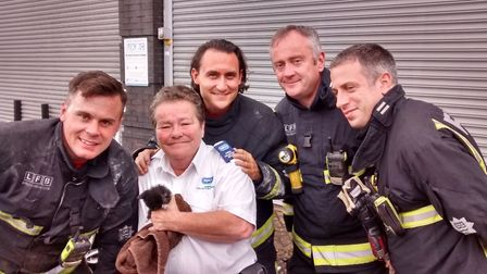 Jill Sanders poses with Ace and the firemen that helped save the kitten Picture: RSPCA