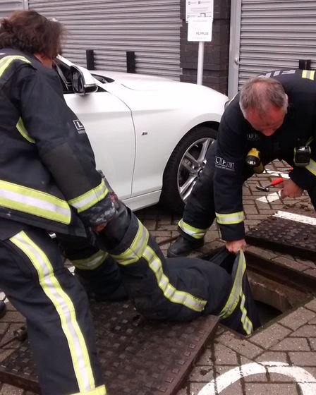 Firemen attempt to rescue Ace who found herself caught in a drain Picture: RSPCA