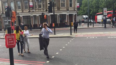 People cross the road at The Angel, where Islington High Street has been closed southbound. Picture: