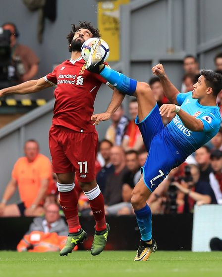Liverpool's Mohamed Salah (left) and Arsenal's Alexis Sanchez battle for the ball during the Premier