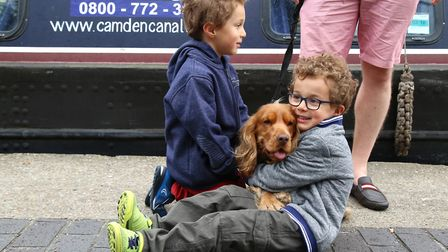 Twins Seb and Leo Sloboda, 5, give their dog Raffi a cuddle at Angel Canal Festival. Picture: Cather