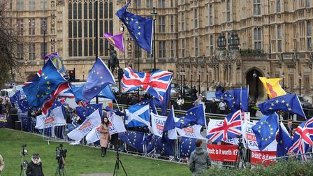 Anti-Brexit and Pro-Brexit protesters fly flags outside the Houses of Parliament. Photograph: Yui Mo