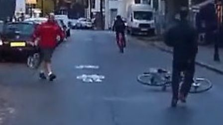 Finally, the suspected thief drops the bike in the road as a postman steps in to help.