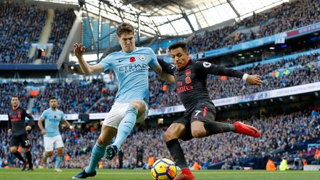Manchester City's John Stones (left) and Arsenal's Alexis Sanchez battle for the ball during the Pre