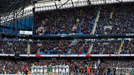Manchester City and Arsenal players observe a minutes silence for Armistice Day during the Premier L