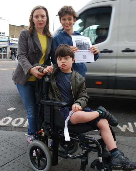 Lucy Morgan, a supporter of the petition, and her children at the crossroads on the Holloway Road. P