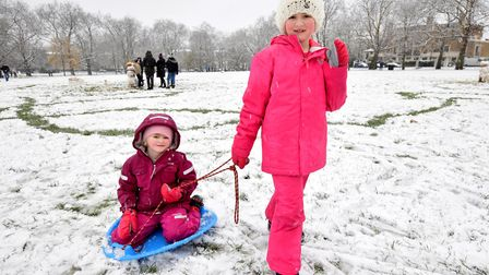 Chloe Cassidy, seven, and Georgia Cassidy, five, play in the snow on Highbury Fields. Picture: Polly