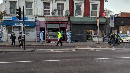 Police and forensics officers in Seven Sisters Road following the assault.