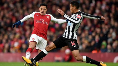Arsenal's Alexis Sanchez (left) and Newcastle United's Isaac Hayden (right) battle for the ball duri