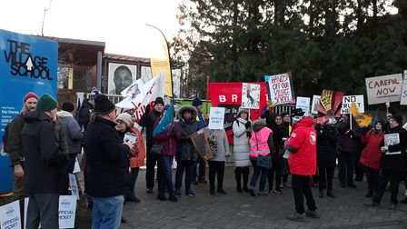 Placard-bearing protestors gathered around the gates of Kingsbury's The Village School this morning.