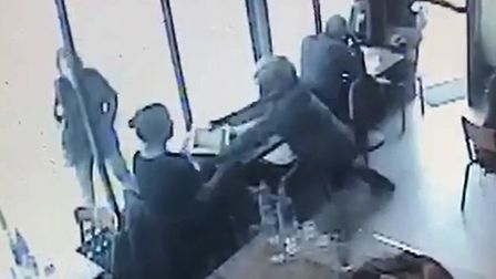 CCTV screenshot of a male bursting into Archway's Bread and Bean cafe and stealing a customer's lapt