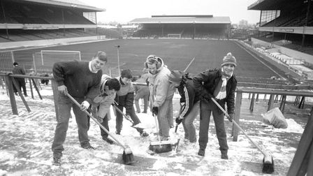 Arsenal fans clear away snow from the terraces at Highbury, after manager George Graham promised a f