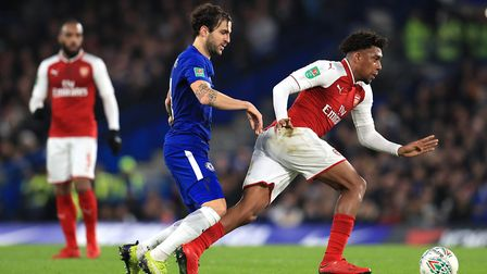 Arsenal's Alex Iwobi (right) battles for the ball with Chelsea's Cesc Fabregas during the Carabao Cu