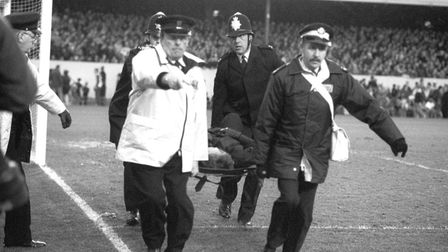 Arsenal v Millwall in 1988: An injured policeman is stretchered away following crowd violence ahead