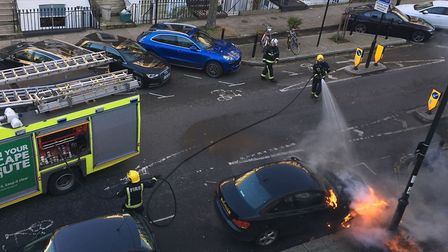 Firefighters tackle the car blaze in Offord Road.