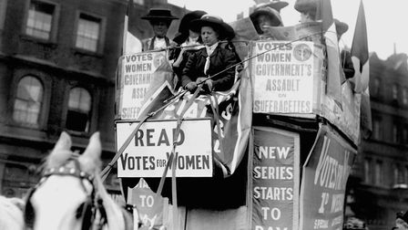 Members of the WSPU on a horse-drawn bus covered with leaflets and posters advertising their cause.