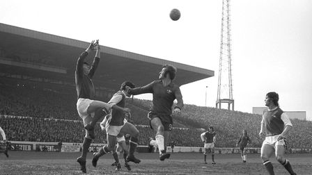 Arsenal goalkeeper Bob Wilson makes a save, watched by his captain Frank McLintock and Chelsea's Pet