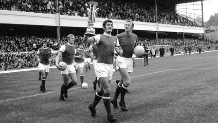 Arsenal captain Frank McLintock (second r) shows off the Inter-Cities Fairs Cup, won the previous se