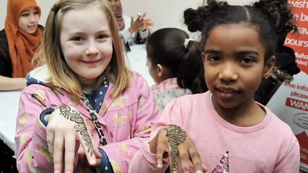 Seven-year-olds Florence Price and Jennah Lokist St George show off their henna painted hands at las