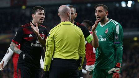 GOAL! A.C. Milan players contest the penalty decision in the Europa League match between Arsenal and