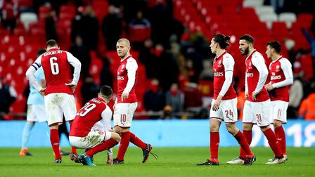 Arsenal's Jack Wilshere stands dejected alongside team-mates after the final whistle during the Cara