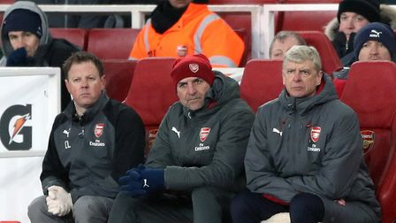 Arsenal manager Arsene Wenger (right) and assistant Steve Bould (centre) appear dejected during the