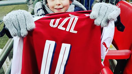 The only happy Arsenal fan this week - Albie Best with Mesut Ozil's match shirt after the 3-0 defeat
