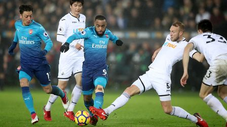 Arsenal's Alexandre Lacazette and Swansea City's Mike van der Hoorn right) battle for the ball (pic