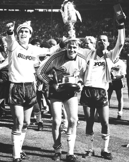Luton Town captain Steve Foster (l) and two goal scorer Brian Stein (r) crown their goalkeeper Andy