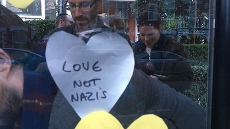 People at the vigil replaced swastikas daubed on a bus stop with hearts. Picture: Nathalie Raffray