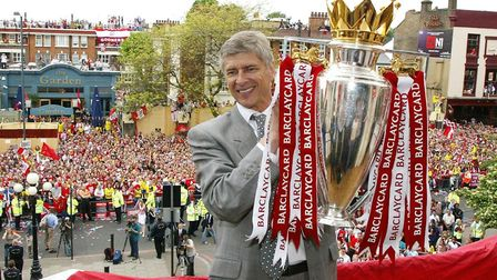 Arsenal manager Arsene Wenger holds up the Premiership trophy to thousands of jubilant fans outside