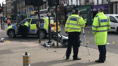 Police in Seven Sisters Road, outside Finsbury Park station, after the moped crash on Tuesday. Pictu