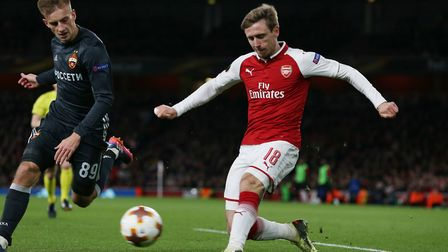 Nacho Monreal of Arsenal puts in a cross while being closed down by Konstantin Kuchaev of CSKA Mosco