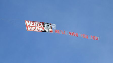 A banner honouring outgoing Arsenal manager Arsene Wenger being pulled by a plane above the ground d
