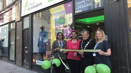 Cllr Dave Poyser cuts the ribbon for Archway's Children's Air Ambulance shop with Farkhanda Hussain,