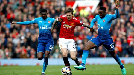 Manchester United's Victor Lindelof (centre) battles for the ball with Arsenal's Danny Welbeck (righ