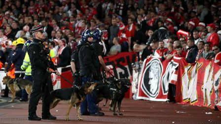 Police with dogs keep watch the FC Koln fans during the Europa League match at the Emirates Stadium,