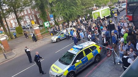A crowd of people outside the police cordon in Upper Street last night after a man in his 20s was st