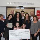 Jack Singer with sister Chloe handing their cheque to Northwick Park Hospital staff