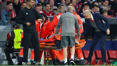 Arsenal manager Arsene Wenger speaks with Arsenal's Laurent Koscielny as he is stretchered off (pic