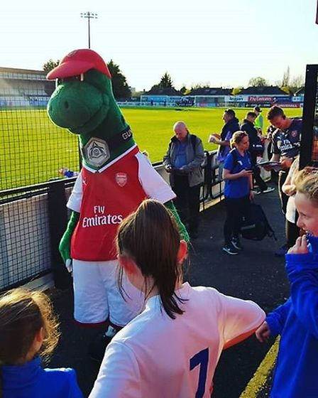The Hitchin Belles with Arsenal mascot Gunnersaurus. CREDIT: @laythy29 Twitter