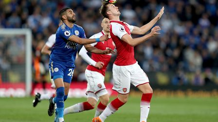 Arsenal's Rob Holding (right) and Leicester City's Riyad Mahrez (left) battle for the ball during th