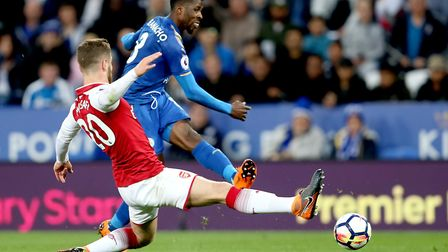 Arsenal's Shkodran Mustafi slides in as Leicester City's Kelechi Iheanacho (right) has a shot during