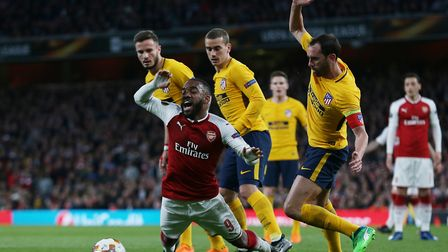 Alexandre Lacazette of Arsenal goes down hoping to win a penalty after a tackle by Diego Godín of At