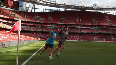 Arsenal's Santi Cazorla (left) jogs round the pitch prior to the UEFA Europa League semi final, firs
