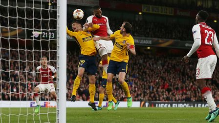 Alexandre Lacazette of Arsenal heads Arsenal in front under pressure from Lucas Hernández and Diego
