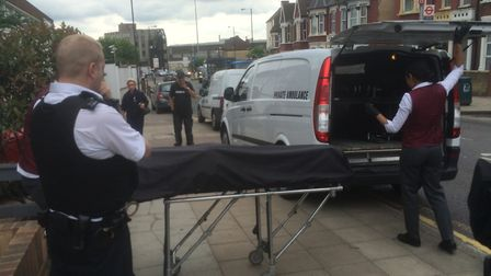 A body is removed from the house in Willesden Lane where a young woman died this morning. Picture: L